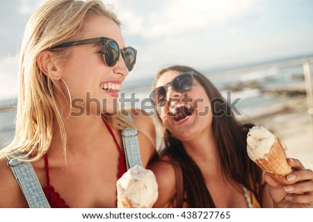 Two young women standing together laughing and eating ice cream. Happy young female friends with icecream enjoying together on a summer day.