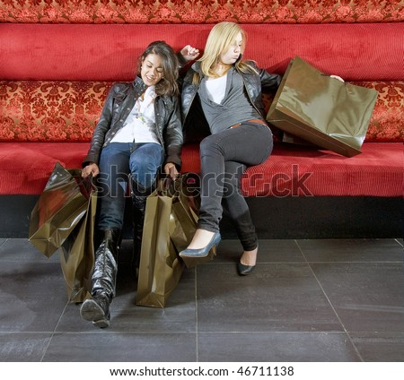 two young women taking a rest in a trendy restaurant after shopping