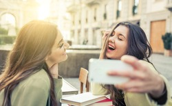 Two young women taking selfie with smart phone in the city center. Happiness concept about people and technology