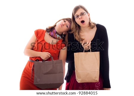 Two young women tired of shopping, isolated on white background.