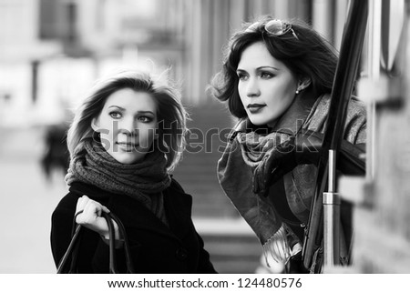 Two young women walking on the city street