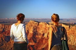 Two young women watching the sunset at the Grand Canyon