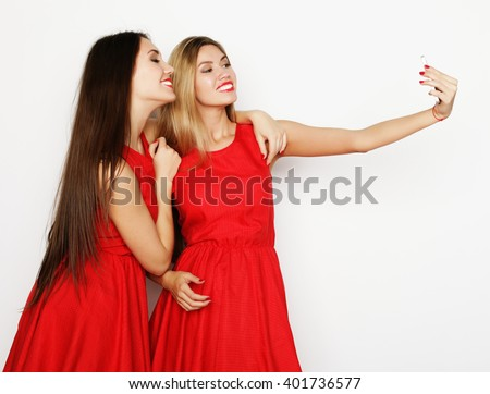 two young women wearing red dress taking selfie