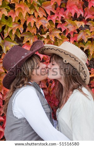 Two young women with cowboy hats kissing each other