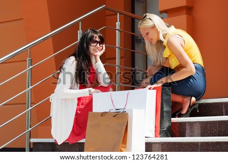 Two young women with shopping bags on the steps
