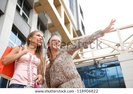Two young  women with shopping bags outdoors.One of girls  shows to  another direction