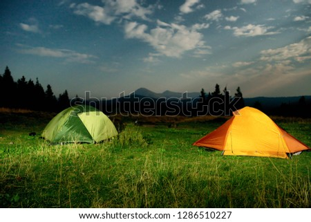 Twp illuminated camping tents on a field at night #1286510227