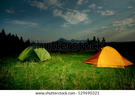 Twp illuminated camping tents on a field at night #529690321