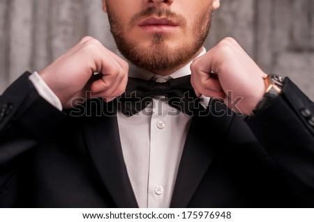 Tying a bow tie. Cropped image of handsome young beard man in formalwear adjusting his bow tie
