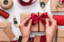 Tying red bow. Gifts wrap up.. Christmas rustic gifts boxes.