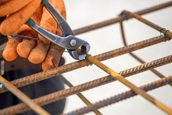 Tying reinforcing steel bars (rebar) for the construction. Tightening wire using a pincers.