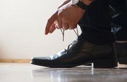Tying shoelaces before work. Elegant men's shoes.