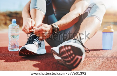 Tying sports shoe. A young sportsman getting ready for athletic and fitness training outdoors. Sport, exercise, fitness, workout. Healthy lifestyle  #577601392