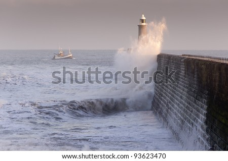 Tynemouth north pier and boat / Waves crashing against Tynemouths pier and lighthouse with fishing boat heading for safety