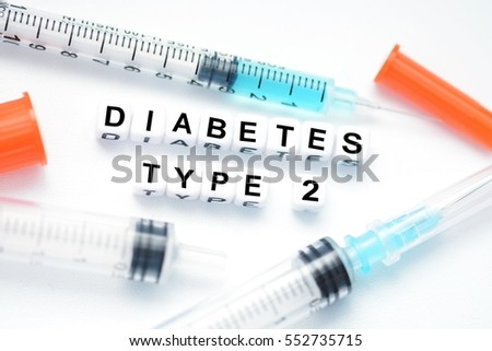 Type 2 diabetes text spelled with plastic letter beads placed next to an insulin syringe #552735715