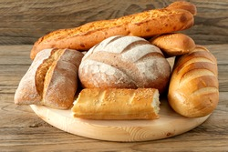 Types of homemade bread on the rustic wooden table. Homemade baked pastry