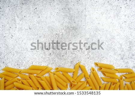 Types of uncooked pasta. Penne pasta uncooked on a light concrete background. Shooting from above. Flat lay, top view, copy space.