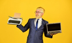 Typewriter against laptop. Businessman use modern technology. Man dyed beard hair yellow background. Buy new modern gadget. Useful device. Modern instead outdated. Connoisseur of vintage values.