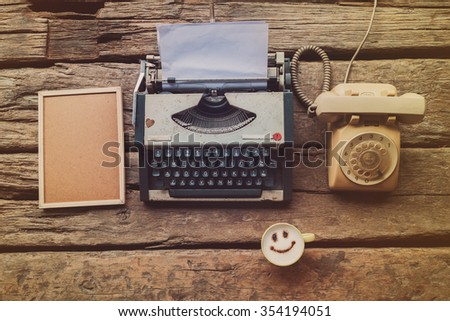 Typewriter coffee and notebook on the wood texture vintage color tone