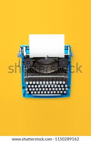 Typewriter machine in retro style on yellow background. Top view.