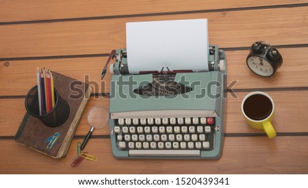 Typewriter on the old wooden desk with coffee cup, writers block office desk