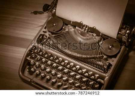 Typewriter ready for use with blank paper installed macro black and white background. Top view. Sepia tone #787246912