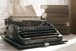 Typewriter with blank page and a stack of books on a writer table background.