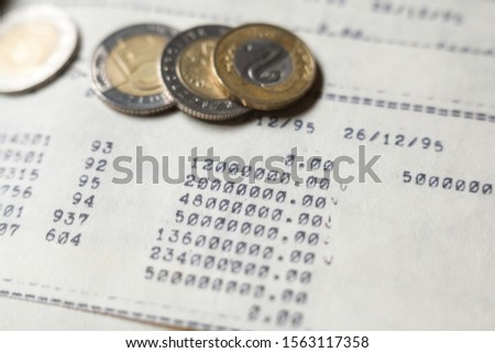 Typewritten calculations and coins. Bookkeeping (accounting). Economy. Financial themes. Money savings and budget. Bank deposits.