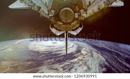 Typhoon and spacecraft above the Earth. Satellite view. Elements of this image furnished by NASA.