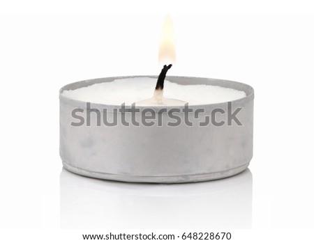 Typical aluminium burning tea candle isolated on white background with shadow reflection. Tea candle with flame and black wick. Tea candle with burning ingle and burned candlewick. Macro photography