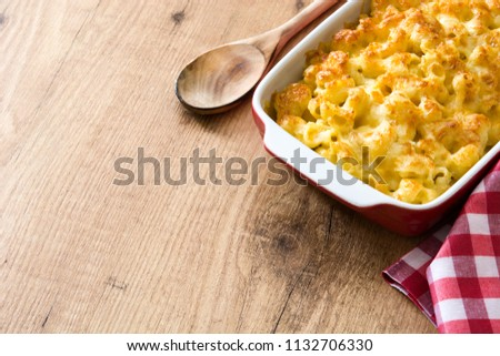 Typical American macaroni and cheese  on wooden table. Copyspace