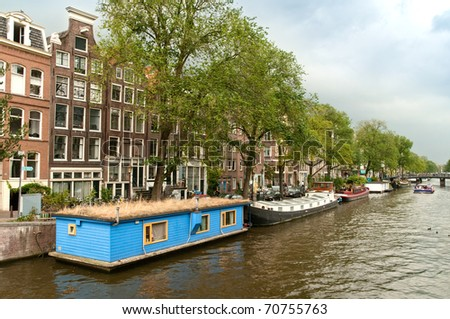 Typical Amsterdam's canal with blue house boat and boats in summer sunny day
