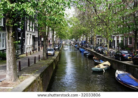 Typical Amsterdam's canal with trees growing along it and boats/bicycles parked everywhere