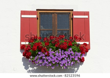 Typical Bavarian Window With Open Wooden Shutters, Decorated With Fresh Flowers