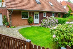 Typical  brick  house with yard and blossoming rhododendrons near Berlin  and skylights with shutters