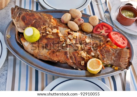 Typical Canarian Roasted sea fish on plate with tomatoes, potatoes, lemon and spices