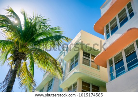 Typical colorful Art Deco architecture with bright backlit palm tree on Ocean Drive in South Beach, Miami, Florida