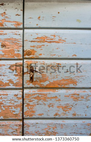 Typical dalmatian old house blue wooden door with paint peeld off #1373360750
