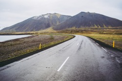 Typical dark gray wet asphalt of beautiful Icelandic roads. Highway by the lake and bold mountains covered by gray clouds. Pale green grass.