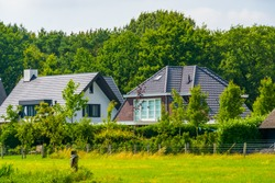 typical dutch architecture, country side houses with forest and grass pasture, Bergen op zoom, The Netherlands