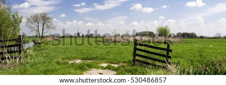 Stock Photo Typical dutch landscape with windmill, green grass, wooden fence, blue sky, white clouds and trees