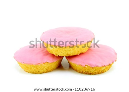 """Typical dutch pastry called """"roze koek""""(pink cake). Its a flat cake with fondant glazing, on a white background."""