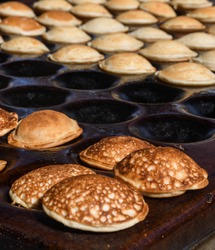 Typical Dutch poffertjes - tiny pancakes-being baked on a heavy cast iron pan being prepared during street food festival, an outdoor event, traditional dessert served with chocolate sauce and sugar