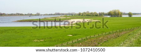 Typical Dutch river Waal panorama landscape with trees, green grass, water. Picture is taken on a nice day in spring. Ideal area for walking, hiking and enjoying Dutch rural environment #1072410500