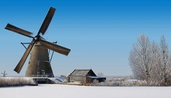 Typical dutch windmill and an old shack in the winter