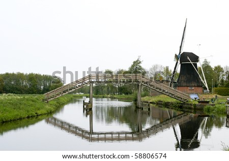 Typical Dutch wooden high bridge above river with windmill and reflection of bridge in water