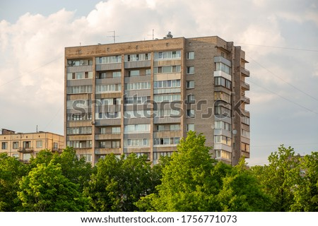 Typical facade of an old brick nine-story building in the post-Soviet countries on a background of green trees.