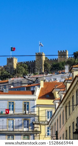 Typical facades  of old buildings with in the background the Saint George Castle in Lisbon, Portugal