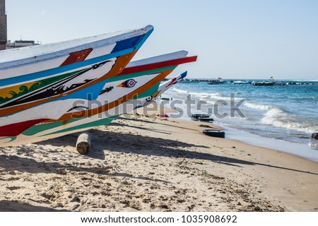 Typical fishing boats in Yoff Dakar, Senegal, called pirogue or piragua or piraga. Colorful boats used by fishermen standing on the beach. #1035908692