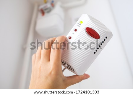 Typical gas sensor in Europe. White gas detector device in hand to prevent gas leaks and provide safety at home. Smoke detecting alarm in the European kitchen. Gas flow meter in the background at home